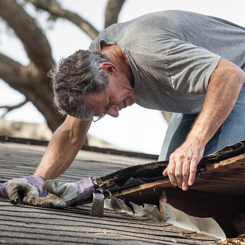 Man working to repair a leaking roof.