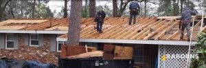 Roofer Working on a Roof With His Team