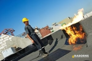 Commercial Roofing Company Employee Repairs a Commercial Roof